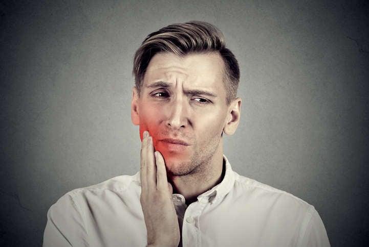 Fotografía de un hombre tocándose la mejilla debido al dolor de un absceso