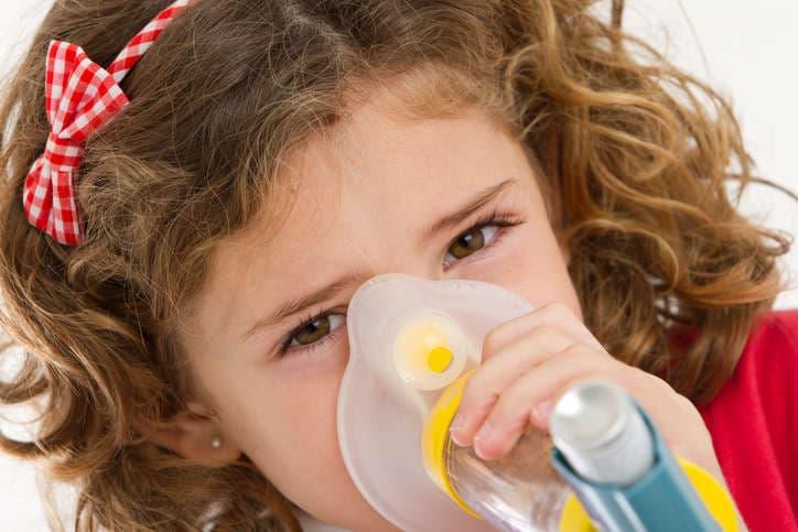 Primer plano de una niña tomando medicación para la bronquiolitis a través de un espaciador