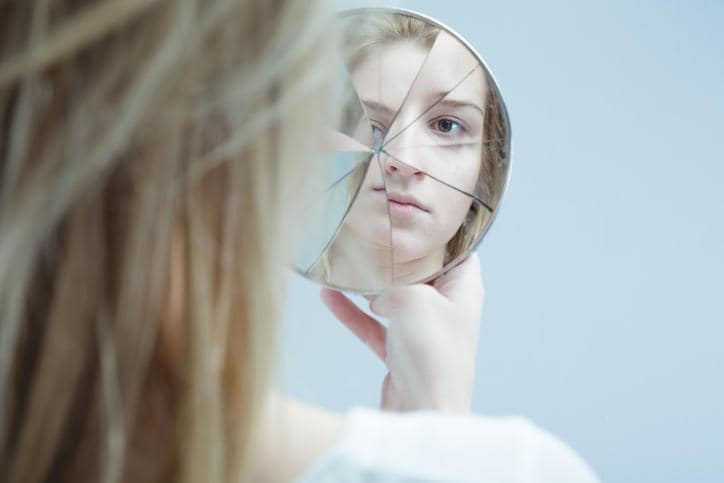 Chica frente a un espejo roto, reflejándola desde varios ángulos