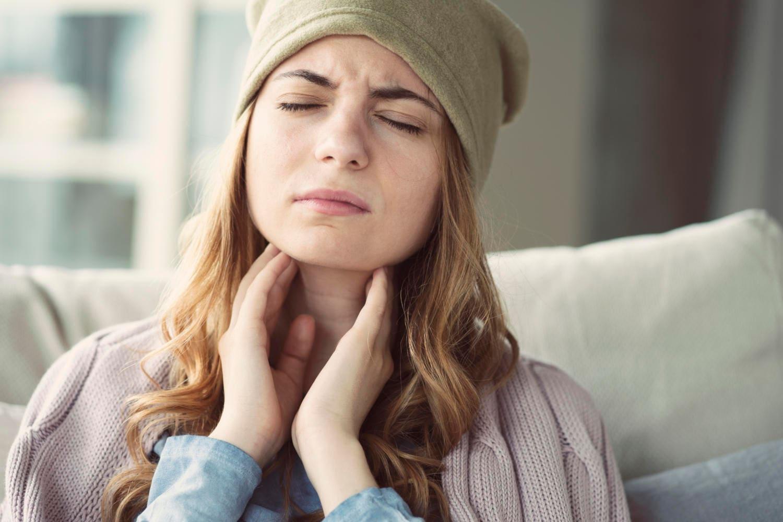 Mujer tocándose la garganta debido al dolor