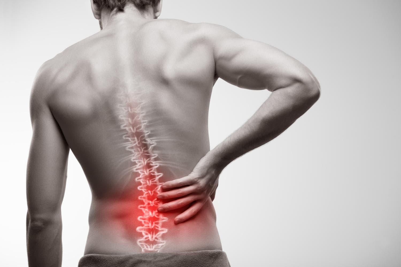 Fotografía en blanco y negro de un hombre tocándose la espalda debido al dolor