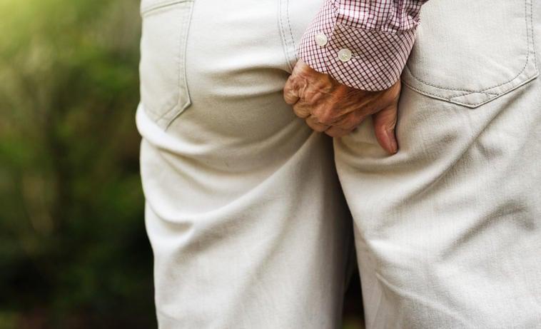 Hombre que muestra picazón en el ano rascándose los pantalones debido a la presencia de oxiuros