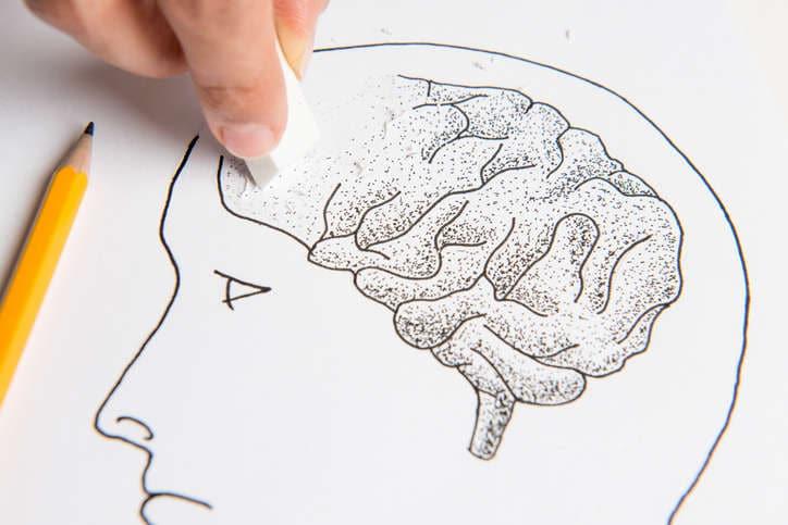 Dibujo esquemático de una cabeza, mientras el diseñador borra parte del cerebro con el borrador como metáfora de la pérdida de memoria.