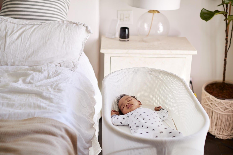 Bebé durmiendo en una cuna junto a la cama de los padres.