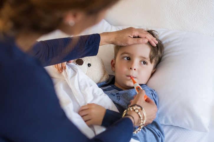 Imagen de una madre midiendo la fiebre de un bebé